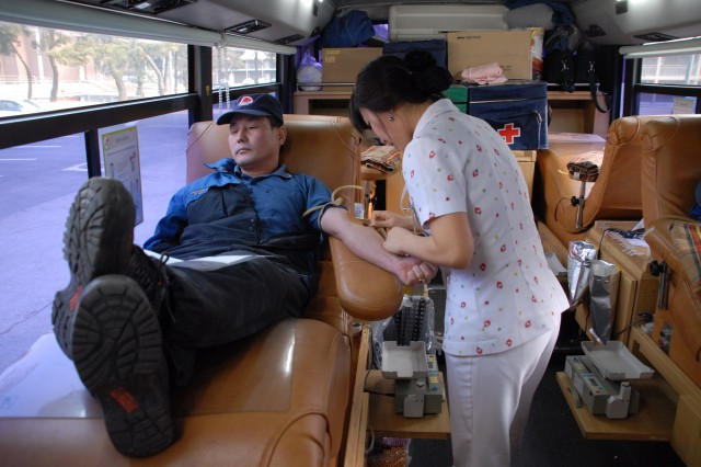 Bae, Jin Young (center) from Korean Red Cross draws blood from Lee, Yong Jae (reclining), DOL employee, during the blood drive held Jan. 9 on Red Cloud outside building 57. Employees of Red Cloud's Directorate of Logistics and Korean Employees Union held a blood drive to benefit Ko, Un Young an elementary school student suffering from leukemia. The child will have a bone marrow transplant with marrow donated by her siblings soon and will need a large amount of blood. For this reason, employees of DOL and the KEU in Area I decided to have a blood drive on post outside of building 57. Employees from all directorates came to give blood.