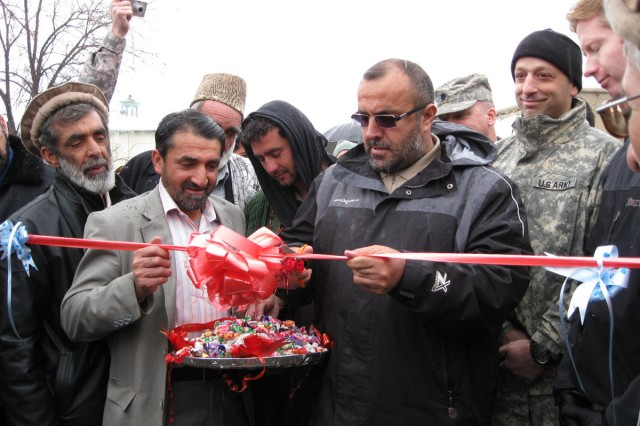Gov. Hajii Bahlol, of Afghanistan's Panjshir province, takes the first of several honorary snips of the red ribbon at the grand opening for Panjshir's Bakshi Khiel Bridge in the province's Rokha district.