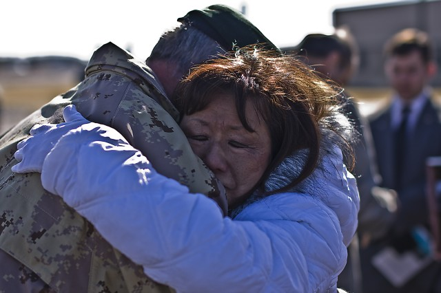 Canadian Army Brig. Gen. Peter Atkinson, III Corps Deputy Commanding General and guest speaker, embraces Jasmine Crowl, mother of Chief Warrant Officer 3 Cornell Chao, at the end of the dedication ceremony of the headquarters buildings of the 1st Air Cavalry Brigade, 1st Cavalry Division, at Fort Hood, Texas, Jan. 28. The 1st ACB buildings are being dedicated to Chao Capt. Mark Resh and for the ultimate sacrifice they gave during Operation Iraqi Freedom 06-08.