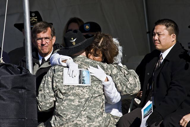 During the dedication ceremony of the 1st Air Cavalry Brigade, 1st Cavalry Division, headquarters buildings, Chief Warrant Officer 2 Jacob Gaston embraces Jasmine Crowl, mother of Chief Warrant Officer 3 Cornell Chao, with son Raymond Chao (right) and  husband Glenn Crowl (left). Gaston was one of the wingmen Chao and Resh laid down their lives for in combat during Operation Iraqi Freedom 06-08, two years ago this day. The building dedication ceremony held on Jan. 28, at Fort Hood, Texas, was to honor that ultimate sacrifice.