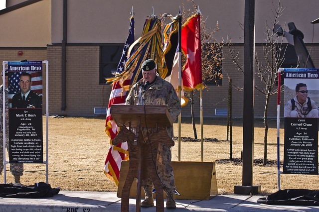 Flanked by banners of Capt. Mark Resh (left banner) and Chief Warrant Officer 3 Cornell Chao (right banner) Canadian Army Brig. Gen. Peter Atkinson, III Corps Deputy Commanding General and guest speaker at the 1st Air cavalry Brigade, 1st Cavalry Division, building dedication ceremony, gives an account of the ultimate sacrifice made by Resh and Chao two years ago during Operation Iraqi Freedom 06-08.
