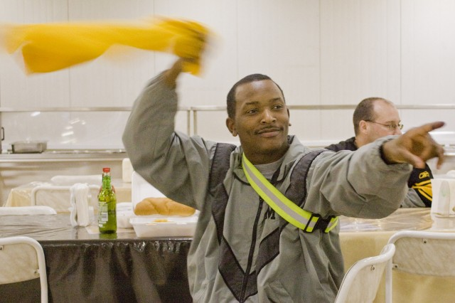 """Sgt. Cyril Illidge, a human resources specialist from the Bronx, N.Y., and the 408th Human Resources Command, waves his """"Terrible Towel"""" while cheering for the Pittsburg Steelers Feb. 2, at Coalition South Dining Facility in Contingency Operating Base Adder."""