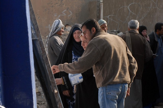 An Iraqi man and his family check a list of possible candidates to vote for while at a polling station during Election Day in Diyala, Iraq, Jan. 31. Voters received a purple finger after their voting preferences were completed. (U.S. Army photo by Spc. Opal Vaughn, 14th Public Affairs Detachment)