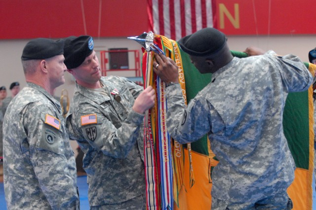 Maj. Gen. Yves Fontaine, commander of the 21st Theater Sustainment Command (left), watches as Col. Mark Spindler, commander of the 18th Military Police Brigade (center), and brigade Command Sgt. Maj. Bernard McPherson attach an Iraq campaign streamer to the brigade's colors during a Jan. 30 ceremony at the Sports Arena on Benjamin Franklin Village in Mannheim, Germany. The ceremony officially marked the end of combat tours in Iraq for the brigade and the 95th MP Battalion.