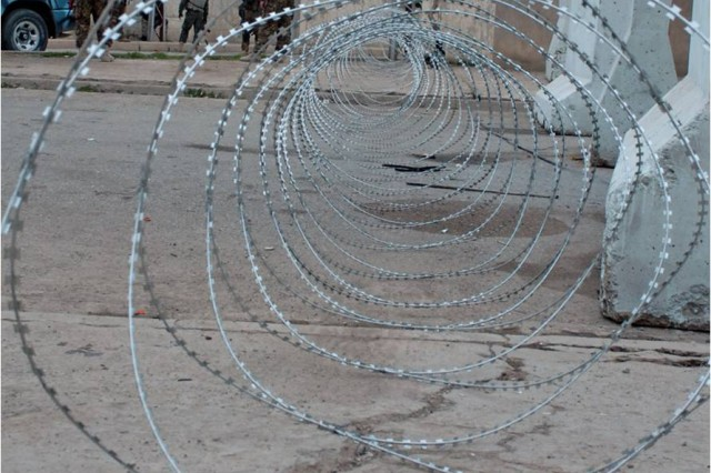 Concertina wire and concrete barriers divide a polling site in Mosul from its surrounding neighborhood during the area's provincial elections Jan. 31. Besides protecting voters, these barriers mark off-limits areas to Coalition Forces who were instructed to avoid the polling sites, putting the Iraqi Security Forces at the front of operations. (Photo by Pfc. Sharla Perrin, 3rd Heavy Brigade Combat Team, 1st Cavalry Division Public Affairs.)
