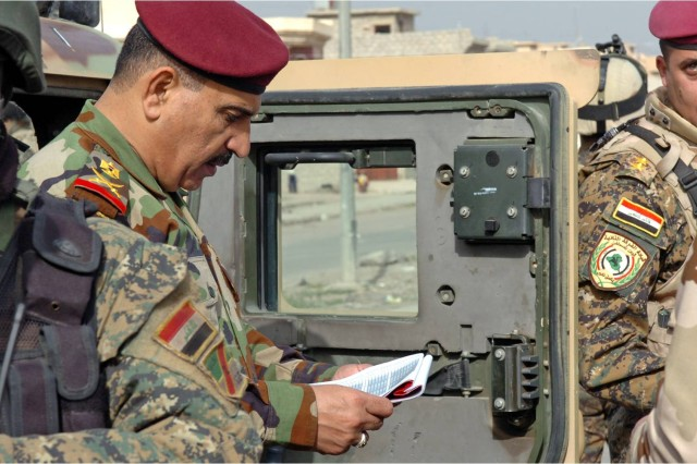 Maj. Gen. Abdulla Abdul Karim Satter Abbas Al, the commanding general of 2nd Iraqi Army Division studies plans for the security of a polling center in Mosul Jan. 31 while touring the area's polling sites. Abdulla was charged with the maintenance and security of the sites and their surrounding neighborhoods. (Photo by Pfc. Sharla Perrin, 3rd Heavy Brigade Combat Team, 1st Cavalry Division Public Affairs.)