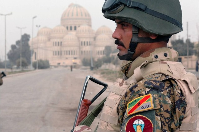 A Soldier with the 2nd Iraqi Army Division personal security detachment is seen with Saddam Hussein's unfinished mosque in the background Jan. 31 during the provincial elections in Mosul. A curfew was placed on all civilian vehicle movement over the span of three days to protect the city's polling sites and voters from potential vehicle-borne improvised explosive devices. (Photo by Pfc. Sharla Perrin, 3rd Heavy Brigade Combat Team, 1st Cavalry Division Public Affairs.)