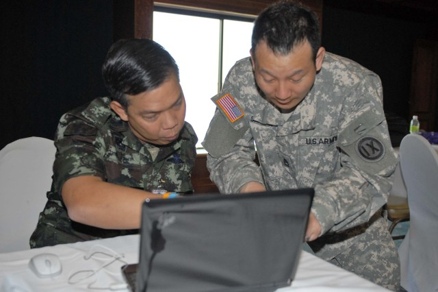 Thai Lt. Col. Chantaman Wuthaya explains his country's plans and operations procedures to Sgt. 1st Class Douglas Sanada, 9th MSC intelligence NCO, during Cobra Gold 2009.  This year is the 28th iteration of a continuation series of military exercises designed to strengthen international ties.