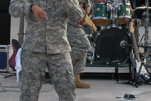 Staff Sgt. William Baez belts out a tune during one of the Army Ground Forces Band's rock band performances at high schools in southern Florida. Band tours, such as the one that occurred at the end of January 2009, serve as a great entry for recruiters into underserved communities.