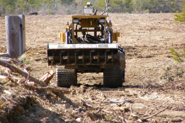 Robotically controlled equipment removes unexploded ordnance on an Army range.
