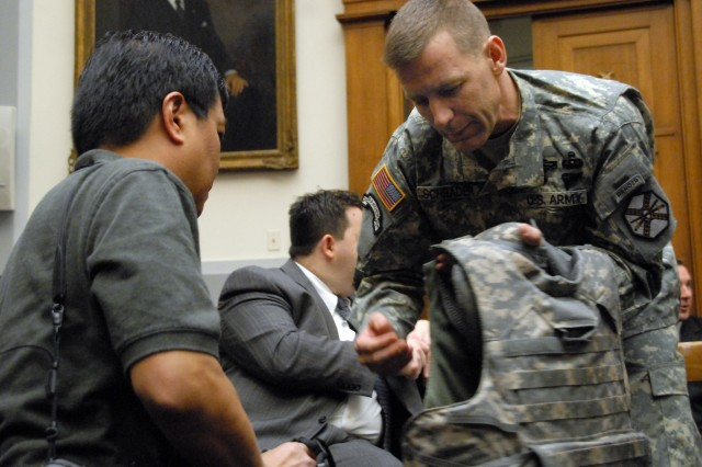 1st Sgt. Patrick Schrader discusses his body armor with a civilian reporter in the Rayburn House Office Building in Washington, D.C.  Both Schrader and Staff Sgt. Fred Rowe attended a hearing before the House Armed Services Committee joint air and land forces and seapower and expeditionary forces subcommittees, Feb. 4.