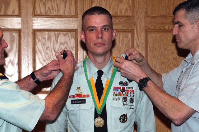 Brigadier Gen. Michael Linnington, commandant of the U.S. Corps of Cadets, right, and Command Sgt. Maj. Anthony Mahoney, USCC senior noncommissioned officer, promote Ryan Goldsmith, USCC equal opportunity advisor, to master sergeant during a ceremony Monday in Washington Hall's Red Reeder Room. During the ceremony, Goldsmith also received the Order of the Marechaussee, an honor bestowed upon outstanding members of the Military Police Corps.