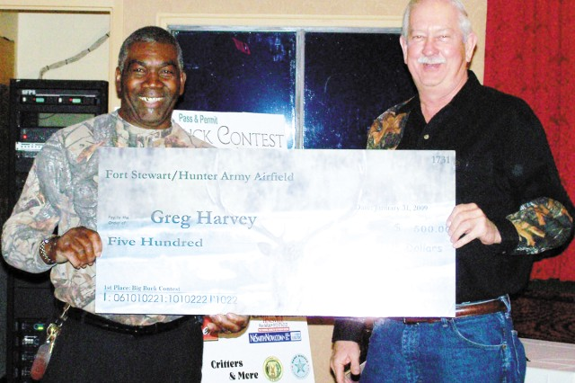 Big Buck Gala coordinator Willie Inman hands a $500 prize check to Big Buck contest winner, Greg Harvey, whose successful hunting season included his prize winning 10-point deer.  The Gala featured displays of wildlife on Fort Stewart-Hunter Army Airfield including boar and deer.