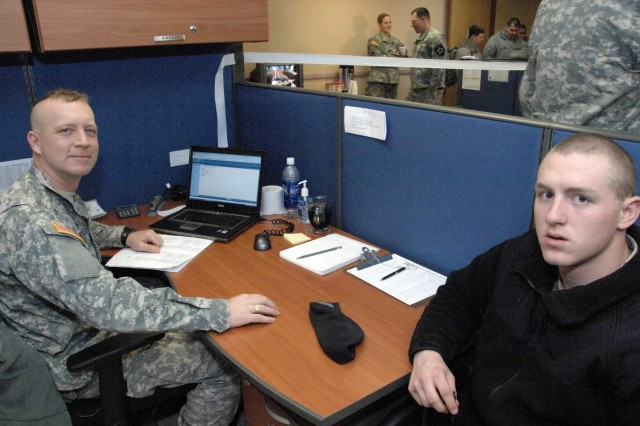 (From left) Tax preparer Pfc. James Rellinger considers the tax options for Pfc. Michael Ream on opening day of the Area I Tax Center in Maude Hall on USAG-Casey Jan. 27. - U.S. Army photo by Jim Cunningham