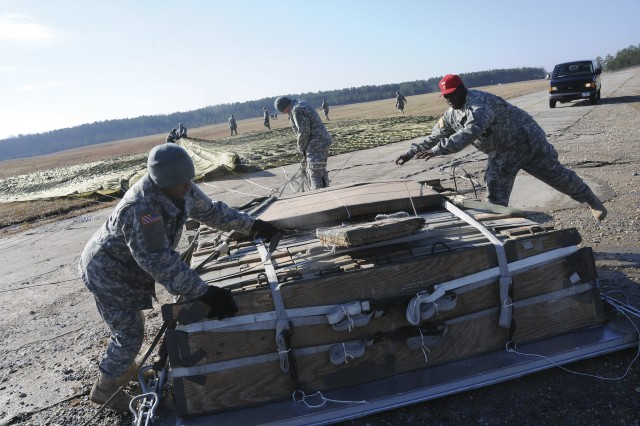 Sgt. 1st Class Donnie James, red hat, helps students recover equipment from a heavy airdrop portion of the training at Fort Pickett, Va.