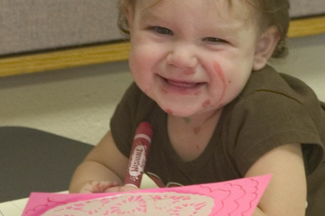 SCHOFIELD BARRACKS, Hawaii - Kloe Chickos, 1, smiles as she continues to decorate a Valentine's Day card for her deployed father. Family members gathered at the Sgt. Yano library, recently, to create a card for their special valentine downrange.