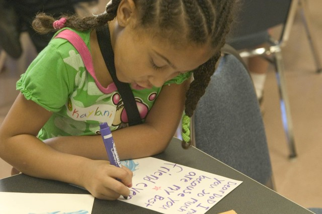 SCHOFIELD BARRACKS, Hawaii - Kaylani Marshall, 7, completes her Valentine's Day card to her father by adding a personal message. Family members gathered at the Sgt. Yano Library for the free Create-a-Card Program to send messages of love to Soldiers downrange.
