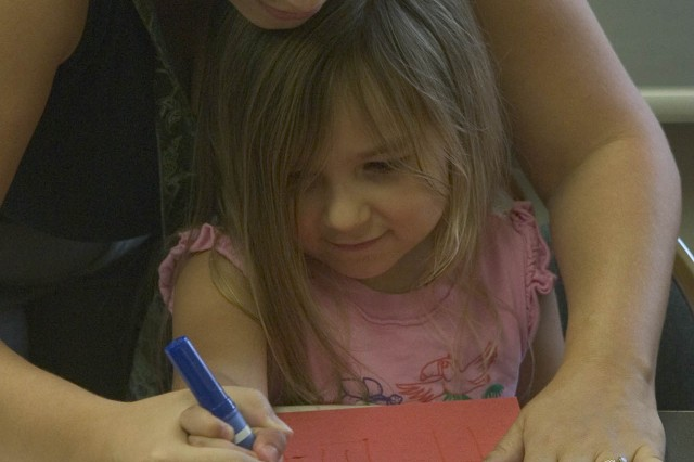 SCHOFIELD BARRACKS, Hawaii - Billie Freitas (left) helps daughter Alexia, 7, write a note to her father. Numerous children and spouses gathered at the Sgt. Yano Library to create a card for loved ones for the upcoming holiday.