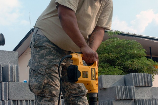 Spc. Andrew Kalaukoa of Makaha, Hawaii drills a hole in the foundation to set rebar in place in the new classroom facility the Hawaii National Guard, 230th Engineer Company, Vertical is building jointly with the Royal Thai Marine Engineer Battalion during the Cobra Gold joint engineering civil assistance mission hosted at the Ban Nong Buatong school in the Chanthaburi District of Thailand Jan. 24 to Feb. 11.