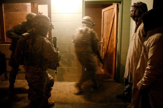 Soldiers from Co. C, 2-3 Inf., enter a building as two role players look on.