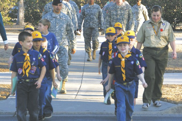Cub Scouts of Pack 23, Den 7 march in front of Army Medical Department Noncommissioned Officer Academy Soldiers Feb. 13 on their way to retreat post's main flagpole.