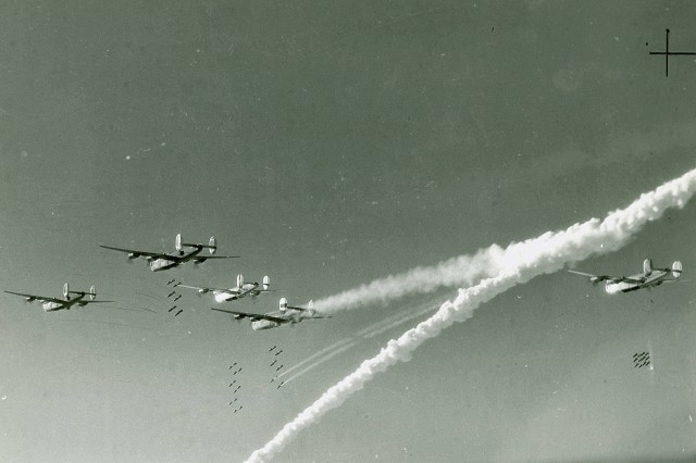 B-24 Liberator heavy bombers drop bombs over France in 1944.  The aircraft trailing smoke in the lower center has been damaged.  The larger smoke trail may mark the path of a downed aircraft. (WW2 Signal Corps Collection).