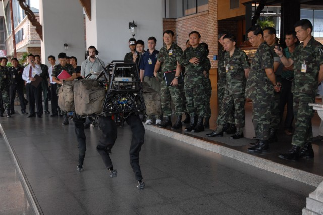 Participants watch a robotic display of a device capable of carrying heavy loads that would normally be carried by Soldiers.