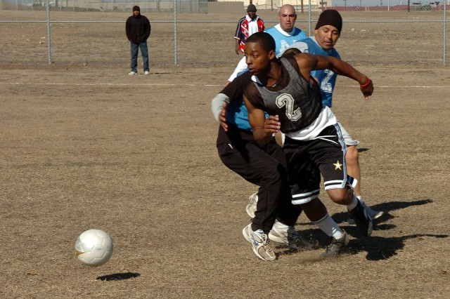Spc. Desean Durham, with the Headquarters and Headquarters Company, Special Troops Battalion, 15th Sustainment Brigade, 13th Sustainment Command (Expeditionary), plays the ball past opponents of the 263rd Maintenance Company, Special Troops Battalion, Jan. 30 during the championship soccer game of the Wagonmaster Stakes competition.