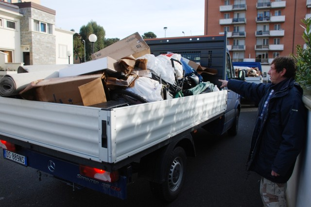 A Department of Public Works employee helps gather up ruined items from service members and their families that were affected by a flash flood on Feb. 6 in Livorno, Italy.