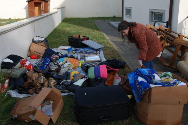 Military spouse Natalie Martinka, searches for a pair of dry shoes amidst items drying from the flood.