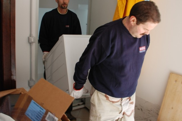 Italian employees from Camp Darby CFMO haul away a washing machine damaged during the flood.
