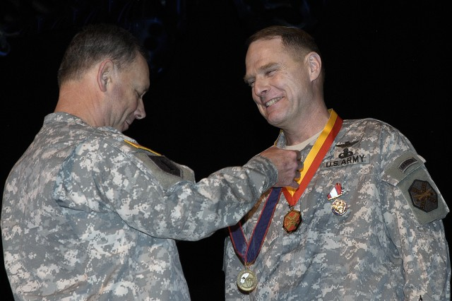Lt. Gen. Robert Wilson, Assistant Chief of Staff for Installation Management and Commanding General of the U.S. Army Installation Management Command, presents one of three awards to Maj. Gen. John A. Macdonald at the Change of Command ceremony at Fort Belvoir's Wallace Theater on Friday, February 6.