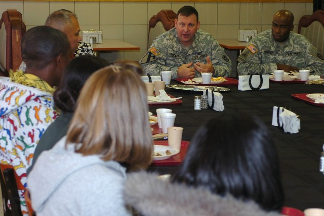 Col. Larry Phelps, the commander of the 15th Sustainment Brigade, 13th Sustainment Command (Expeditionary), talks to local high school students during lunch at the Freeman CafAfA Dining Facility Jan. 28.