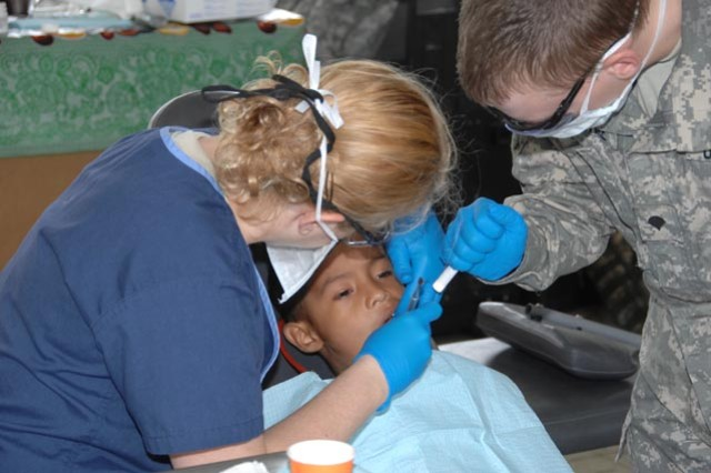 Army Capt. Allison Wright, a dentist with the 7218th Medical Support Unit, Louisville, Ky., left, performs an extraction with Spc. Shaun Macintire, on a Panamanian boy during a Medical Readiness Training Exercise in Canitas, Panama on Feb. 2.