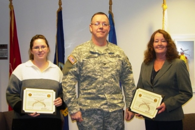 CAAA Commander Col. Charles Kibben presents the certificates of recognition to Security Specialists Judy Brown (left) and Leah Clinton (right) naming them as members of the 2009 Army Antiterrorism Honor Roll for their efforts directed toward protecting people and Army missions from terrorist attacks.