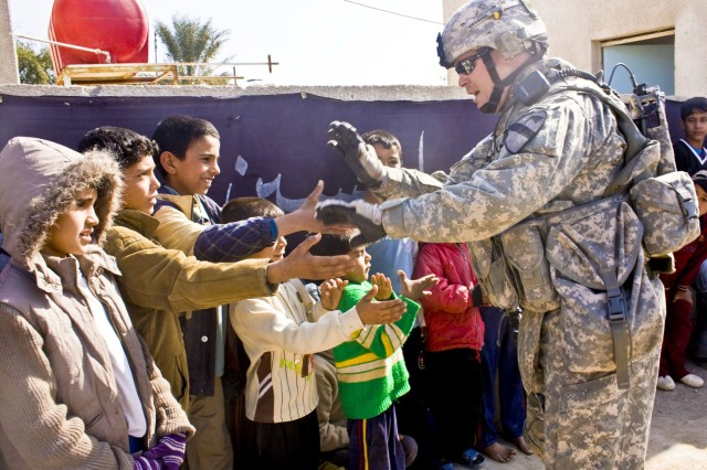 A Soldier from the 1st Squadron, 9th Cavalry Regiment, 4th Brigade Combat Team, 1st Cavalry Division, plays with Iraqi children waiting in line during a combined medical engagement near Forward Operating Base Hunter Jan. 30.