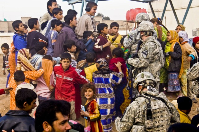Combat medics from the 1st Squadron, 9th Cavalry Regiment, 4th Brigade Combat Team, 1st Cavalry Division, hand out clothing, shoes and coloring books to the locals living near Forward Operating Base Hunter during a combined medical engagement Jan. 30.