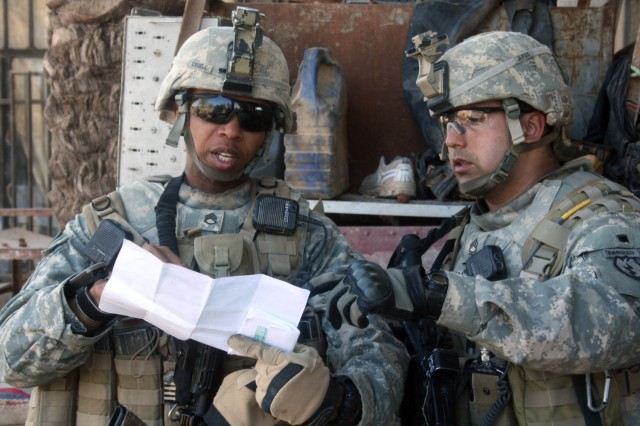 HUSSANIYAH, Iraq - Sgt. 1st Class James Burciaga (right), of West Covina, Calif., and Staff Sgt. Rodriguez Cruell, of Greenville, S.C., review their map of the Hussaniyah area Feb. 3, during a combined air assault mission with members of the 2nd Brigade, 1st Iraqi National Police Division. Burciaga, an infantry platoon sergeant, and Cruell, an infantry squad leader, are both with Company A, 1st Battalion, 27th Infantry Regiment, currently attached to 3rd Brigade Combat Team, 82nd Airborne Division, Multi-National Division-Baghdad.