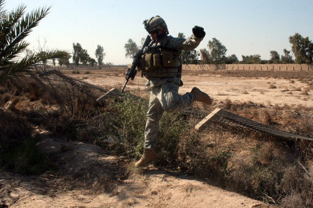 HUSSANIYAH, Iraq - Sgt. Jeremiah Sullivan, of St. Joseph, Mich., leaps off of a downed fence after using it to cross a canal during a combined air assault operation with members of the 2nd Brigade, 1st Iraqi National Police Division during Operation Gunslinger Bonzai XXX, Feb. 3 in the Hussaniyah Nahia. Sullivan is an infantry team leader assigned to Company A, 1st Battalion, 27th Infantry Regiment, currently attached to 3rd Brigade Combat Team, 82nd Airborne Division, Multi-National Division - Baghdad.