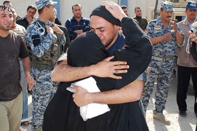 JOINT SECURITY STATION AL JADIDA, Iraq - A released detainee hugs his mother during Operation Lions Return Feb. 7 at Joint Security Station Al Jadida located in the Al Karradah district of eastern Baghdad. The Operation Lions Return program returns former criminals back to their families and provides steady employment.  A total of 24 former detainees were released back to their families during the ceremony.