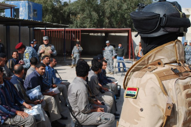 JOINT SECURITY STATION AL JADIDA, Iraq - A National Police officer assigned to the 4th Brigade, 1st NP Division, oversees former detainees during Operation Lions Return Feb. 7 at Joint Security Station Al Jadida, located in the Al Karradah district of eastern Baghdad.  A total of 24 former detainees were released back to their families during the ceremony.