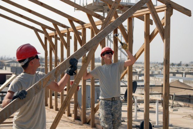CAMP VICTORY, Iraq - Pvt. Curtis Nordby, (right) of Pineville, La., and Pvt. Chip Normand, of  Marksfield, La., use teamwork to dismantle a rotting shade structure on top of the 225th Engineer Brigade headquarters overlooking Camp Victory, Baghdad Feb. 7.  Curtis and Chip are members of the 225th Eng. Bde., 1st Cavalry Division, Multi-National Division-Baghdad.  The Louisiana-based 225th Eng. Bde. will command more than 1,000 Soldiers from the Mississippi National Guard and Fort Polk, La., for the next ten months.