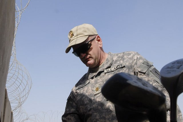 """Maj. Matthew Dabbs, a native of Jacksonville, Ala., operations officer, 2nd Heavy Brigade Combat Team, 1st Infantry Division, Multi-National Division-Baghdad, inspects golf clubs at the new """"Dagger"""" driving range on Camp Liberty Feb. 8. Brigade leaders celebrated the grand-opening of the range by smacking a few balls into the range net themselves."""