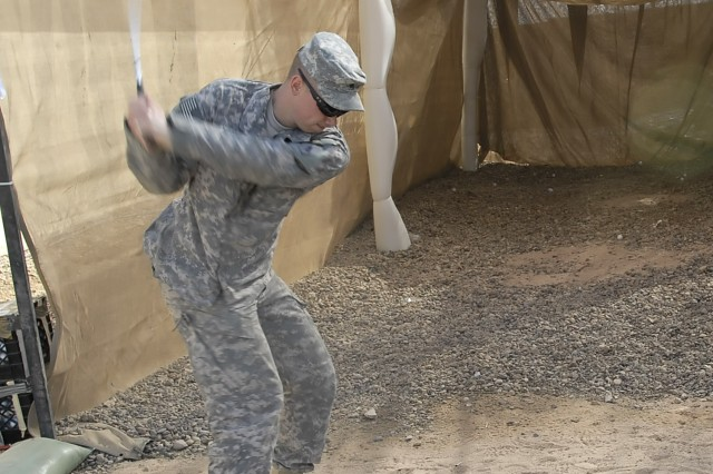 """Sgt. Ryan Greve, of Charlotte, N.C., Headquarters Company, 2nd Heavy Brigade Combat Team, 1st Infantry Division, Multi-National Division-Baghdad, shows off his golf swing at the new """"Dagger"""" driving range on Camp Liberty Feb. 8. The new range is a way for golf-loving Soldiers to hone their driving skills after work."""