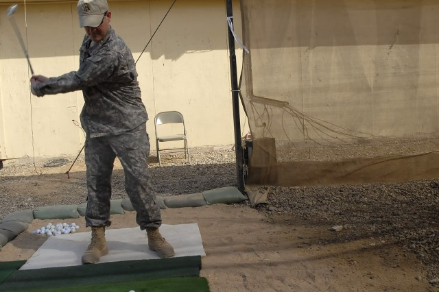 """Lt. Col. Christopher Beckert, from Madison, Conn., deputy commander, 2nd Heavy Brigade Combat Team, 1st Infantry Division, Multi-National Division-Baghdad, practices his drive at the newly installed """"Dagger"""" driving range at Camp Liberty Feb. 8.  A veterans group in Beckert's home state donated the necessary equipment to make use of the range."""