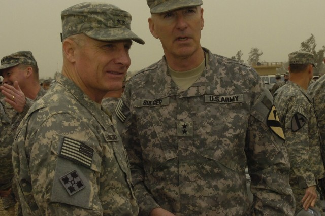 CAMP LIBERTY, Iraq - Maj. Gen. Daniel Bolger (right), commanding general of 1st Cavalry Division, Multi-National Division-Baghdad,  talks to Maj. Gen. Jeffery Hammond, commanding general of 4th Infantry Div., during the transfer of authority ceremony at Camp Liberty in Baghdad Feb. 10. This is the third time both Fort Hood, Texas-based units transferred authority as the headquarters element of MND-B to each other.