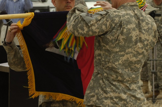 CAMP LIBERTY, Iraq - Command Sergeant Major John Gioia (left), senior enlisted leader of 4th Infantry Division, and Maj. Gen. Jeffery Hammond, commanding general of 4th Inf. Div., case the division's colors during the transfer of authority ceremony at Camp Liberty in Baghdad, Feb. 10. The 4th Inf. Div., is heading home after completing its 15-month tour of Duty in Iraq and is being replaced by the 1st Cavalry Div.