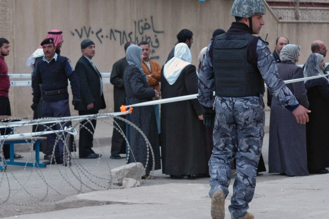 An Iraqi Policeman directs pedestrian traffic at a polling site in Mosul, Iraq on Jan. 31, the day of the country's provincial elections. The sites were secured and maintained by members of the Iraqi Security Forces.