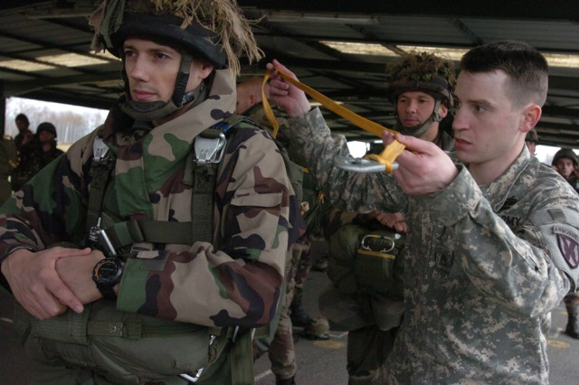 Staff Sgt. David W. Beville, a jumpmaster with the 5th Quartermaster Company, performs a jumpmaster's performance inspection on a French paratrooper at the French Parachute School Feb. 2 in Pau, France.  Forty French paratroopers were awarded U.S. jump wings upon the completion of their training.
