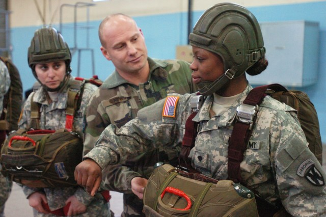 Adjudant Loic Neveu, a French parachute instructor at the French Parachute School, adjusts the parachute harness on Spc. Irene Lenge, a parachute rigger for the 5th Quartermaster Company, at the French Parachute School during a pre-jump training Feb. 3. The 10 U.S. Soldiers, who participated in the combined jump, were awarded French jump wings upon the completion of their training.